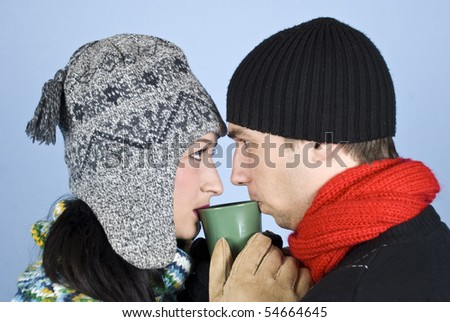 Couple of young people dressed in winter clothes with hats on heads,sweaters standing face to face and looked at each other drinking a hot drink from same mug - stock photo