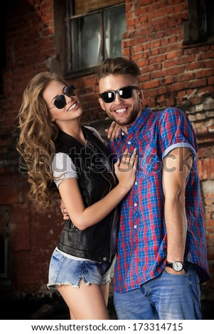 Couple of young people in jeans clothes posing outdoors over brick wall. - stock photo