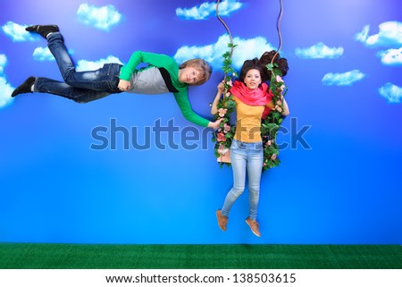 Couple of young people in love flying in the sky. - stock photo