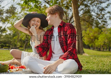 Couple of young people male and female in the park sitting on the grass - stock photo