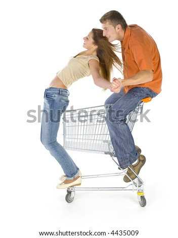 Couple of young people riding by trolley. Having fun. Isolated on white in studio. Holding hands. Side view
