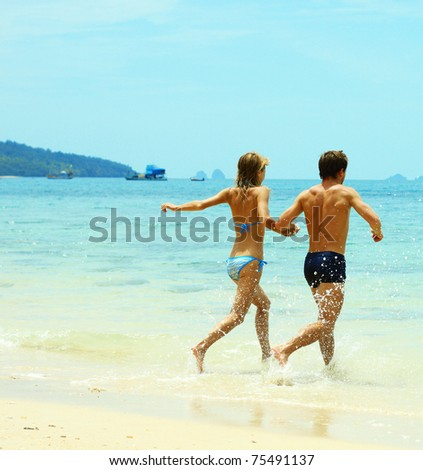 Couple of young people running to the blue sea - stock photo