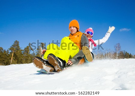 couple of young people  slide downhill together on mountain holiday - stock photo