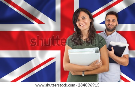 Couple of young students with books over English flag - stock photo