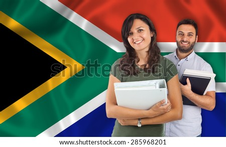Couple of young students with books over South Africa flag - stock photo