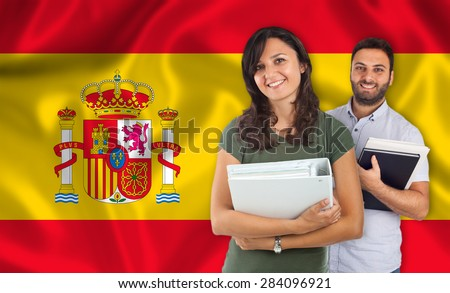 Couple of young students with books over spanish flag - stock photo