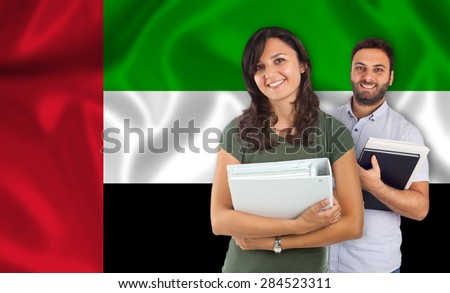 Couple of young students with books over United Arab Emirates flag - stock photo