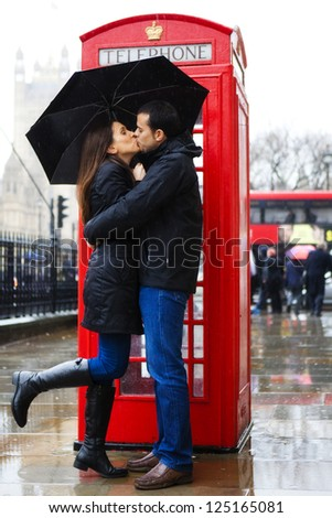 Couple of young tourist kissing in London under an umbrella. She is lifting her leg in a cute way. - stock photo