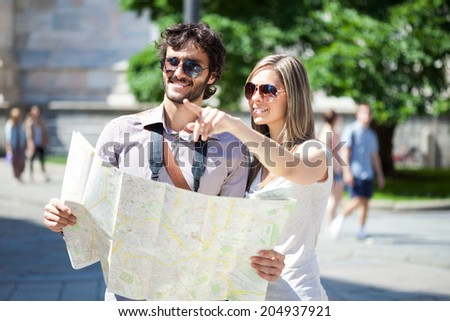 Couple of young tourists reading a map - stock photo