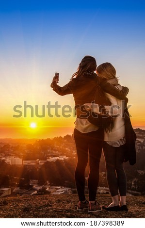 Couple of young women best friends taking a selfie during sunset at Twin Peaks in San Francisco - Teenager girls having fun together outdoors - stock photo