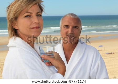 Couple on a beach in bathrobes - stock photo