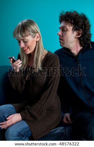 couple on a black leather couch with a cell phone - stock photo