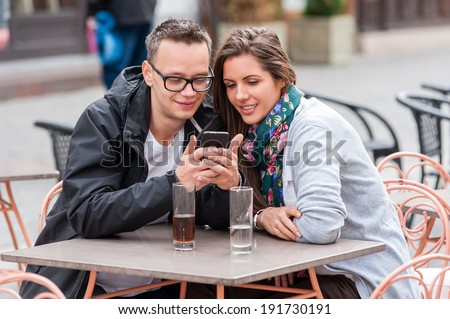 Couple on a coffee shop terrace drinking, watching on the phone,surfing the web , looking at photos on mobile phone. ,talking, having fun laughing smiling happy - stock photo