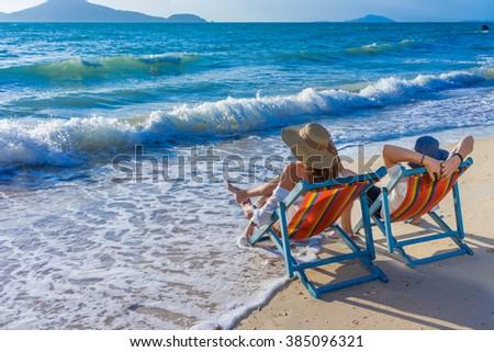 Couple on a deckchair at the tropical beach - stock photo