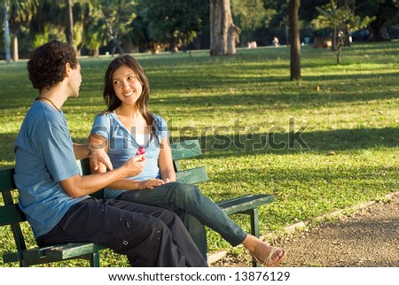 Couple on a park bench gazing into each others eyes. Horizontally framed shot.