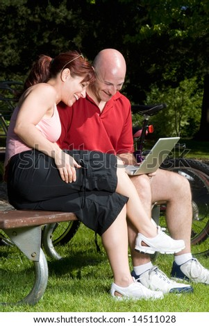 Couple on a park bench laugh as they look at a laptop computer, their bikes are in the background. Vertically framed photograph - stock photo