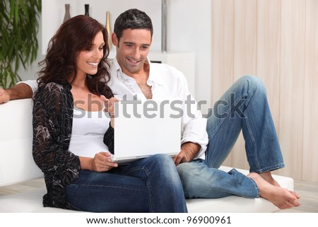 Couple on a sofa with a laptop - stock photo