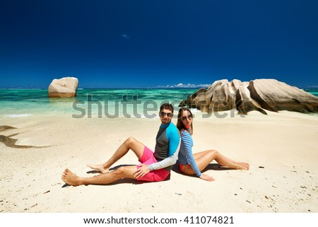 Couple on a tropical beach at Seychelles wearing rash guard - stock photo