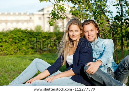 couple on a walk, sit on the grass in the park - stock photo
