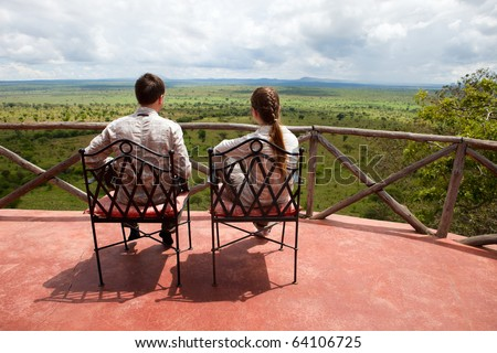 Couple on balcony of safari lodge - stock photo