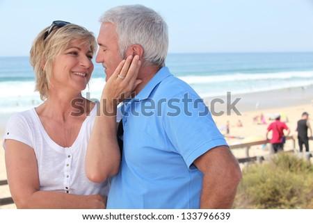 Couple on beach front - stock photo