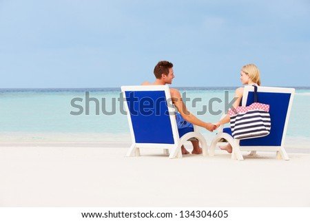 Couple On Beach Relaxing In Chairs - stock photo