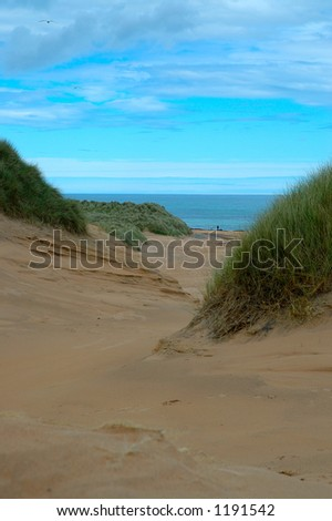 Couple on beach seen through sand dunes - stock photo