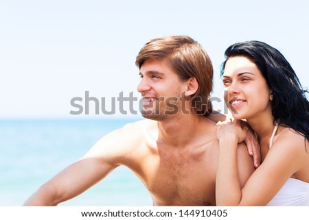 Couple on beach summer vacation, beautiful young happy couple love smiling embracing, man and woman smile over sea blue sky, concept ocean holiday travel looking side to copy space