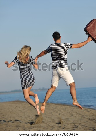 couple on beach with travel bag representing freedom and funny honeymoon concept - stock photo