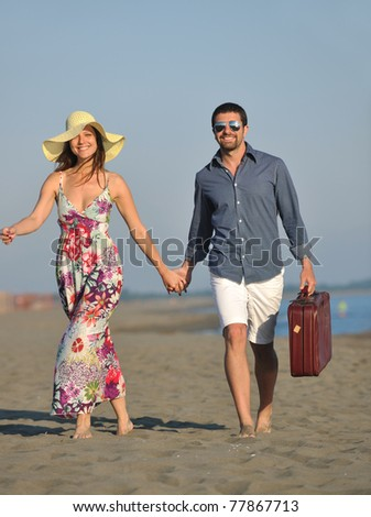 couple on beach with travel bag representing freedom and funny honeymoon concept