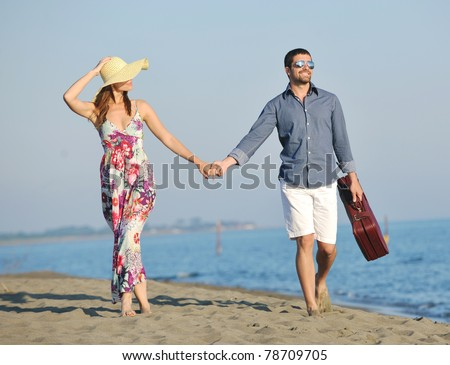 couple on beach with travel bag representing freedom and funy honeymoon concept - stock photo