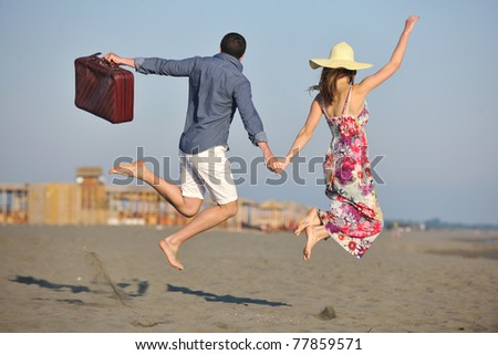 couple on beach with travel bag representing freedom and honeymoon concept - stock photo