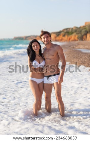 Couple on beach, Young happy man and woman sea shore smiling romantic summer ocean vacation - stock photo