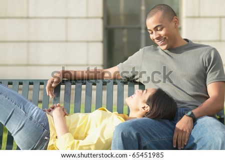 Couple on bench together - stock photo
