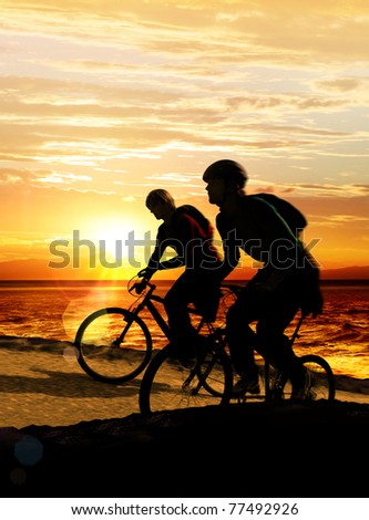 Couple on bicycles on the brink of a rock near sea - stock photo