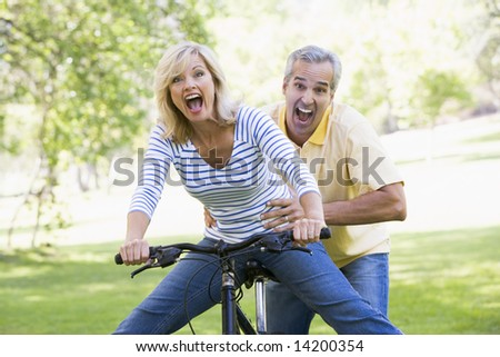 Couple on bike outdoors smiling and acting scared - stock photo