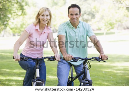 Couple on bikes outdoors smiling - stock photo