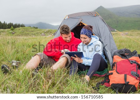 Couple on camping trip using a digital tablet outside their tent - stock photo