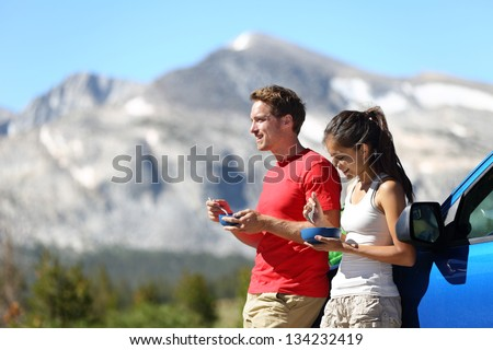 Couple on car road trip travel eating lunch break outdoors smiling happy. Multiracial couple, Asian woman, Caucasian man People in Yosemite National Park, California, United States. - stock photo