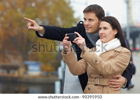 Couple on city trip taking pictures with mobile phone - stock photo