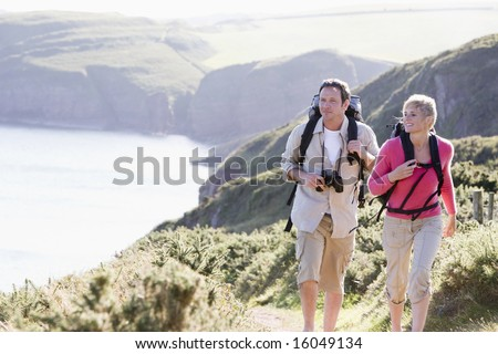 Couple on cliffside outdoors walking and smiling - stock photo