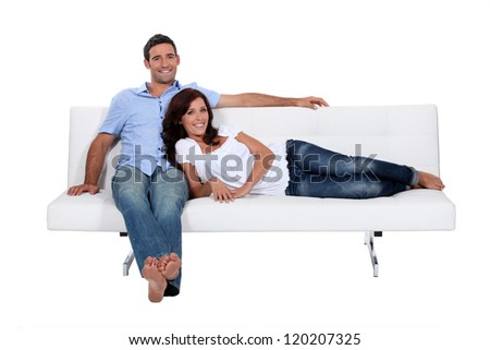 Couple on couch comfortably installed - stock photo