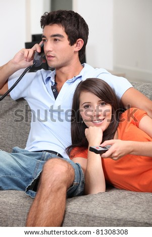 Couple on couch watching television - stock photo