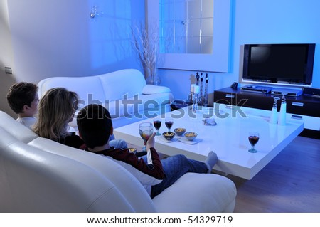 Couple on couch watching TV - stock photo