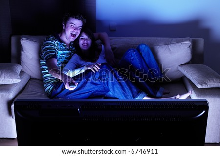 Couple on couch watching TV - having a great time - stock photo
