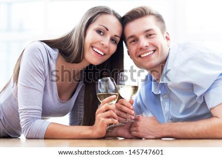 Couple on floor drinking wine - stock photo