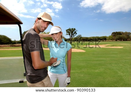 Couple on golf course with cart - stock photo