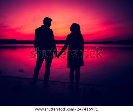 couple on lake shore - stock photo