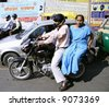 couple on motorcycle in traffic, delhi, india - stock photo