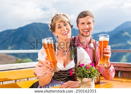 Couple on mountain hut drinking wheat beer, in the background alpine scenery - stock photo